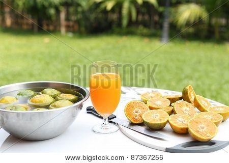 Glass Of Freshly Pressed Orange Juice With Sliced Orange Half On Wooden Table
