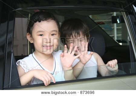 Boy & Girl Waving In The Car