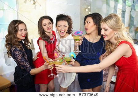 girls clinking glasses of cocktails at the party