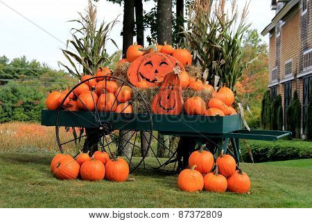 Inviting scene of pumpkins and Jack-O-Lanterns in big green wagon