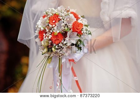 Bride Holding A Wedding Bouquet With White And Red Flowers