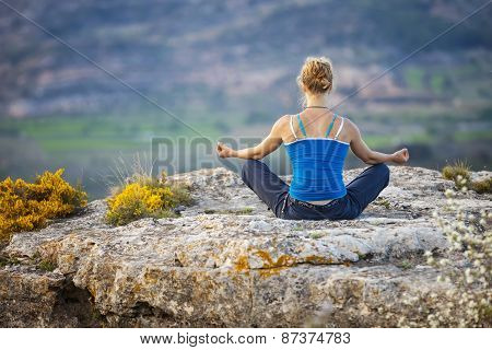Woman sitting on a rock and enjoying valley view