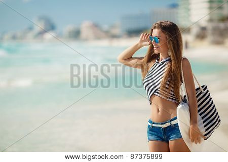 Portrait of happy sexy girls with beach bag posing against the sea.