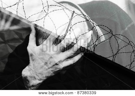 Multiple (dual) man finding himself behind a barbed wire prison.