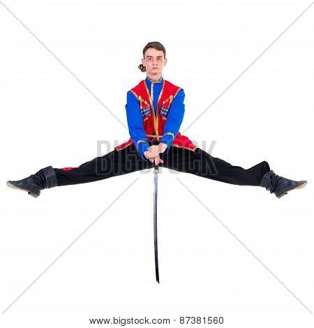 Russian cossack dance. Young dancer jumping over a sword