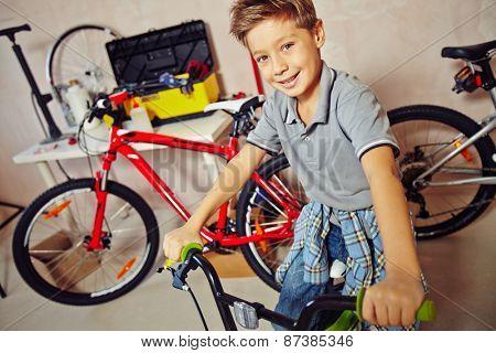Cute boy sitting on bicycle in garage