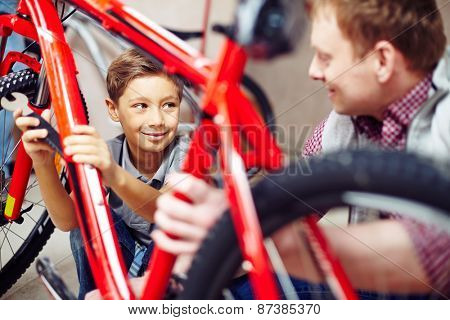 Happy lad looking at his father while helping him in garage