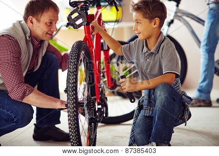 Young man showing his son how to repair bike