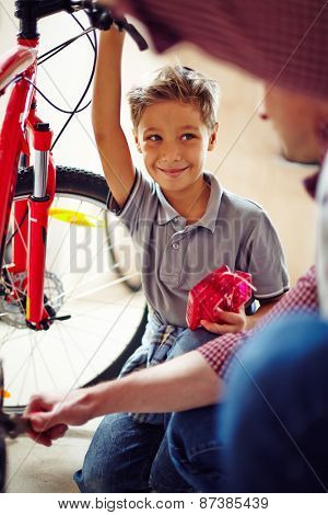 Happy little boy looking at his father in garage