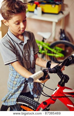 Adolescent boy looking at bicycle