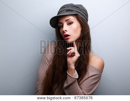 Sexy Female Model In Cap Flirting On Blue Background