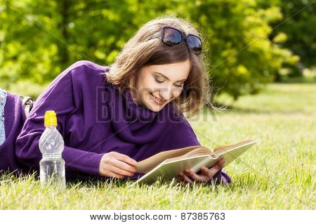 Happy Woman Reading Book Lying Down On Grass