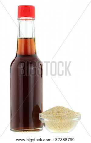 A bottle of cold pressed Sesame oil next to a bowl of white Sesame seeds, isolated on white background