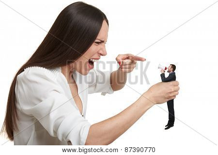displeased woman holding small man in hand and they shouting at each other. isolated on white background