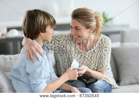 Mother giving money to adolescent for reward