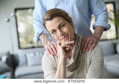 Portrait of mature woman, husband's hands on shoulders