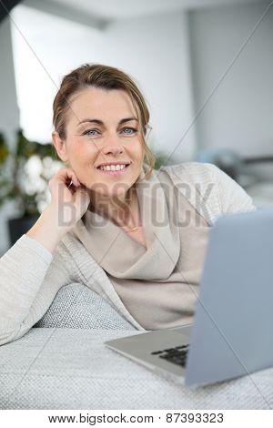 Mature woman sitting in sofa an websurfing with laptop