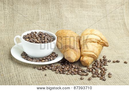 White Porcelain Cup Filled With Coffee Beans, Two Croissants