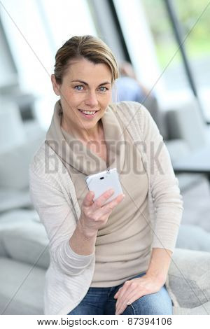 Mature woman sending message with smartphone