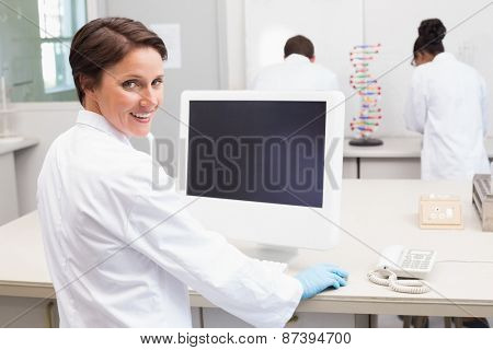 Smiling scientist using computer while colleagues working in the laboratory