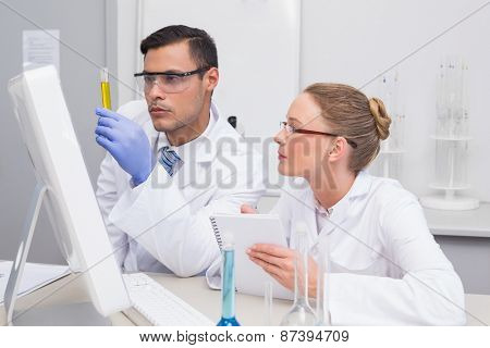 Scientists examining yellow precipitate in tube in the laboratory