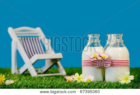 Three Bottles Of Milk With A Lounge Chair In The Grass