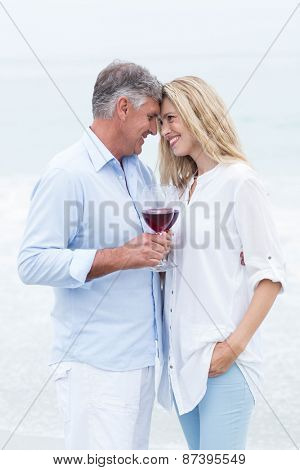 Happy couple smiling at each other and toasting at the beach