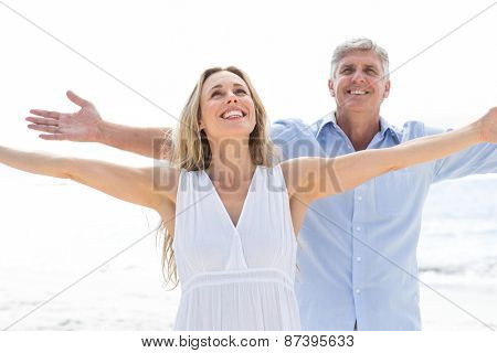 Happy couple standing by the sea arms outstretched at the beach