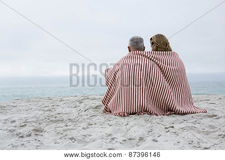Happy couple sitting on the sand with blanket around them at the beach