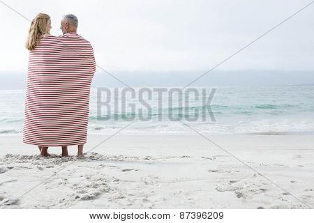 Happy couple hugging each other and looking at the sea with blanket around them at the beach