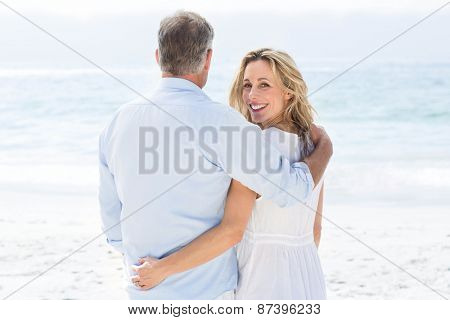Happy couple standing by the sea arms around at the beach