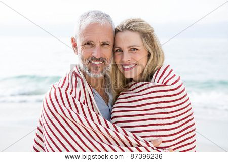 Happy couple smiling at camera with blanket around them at the beach