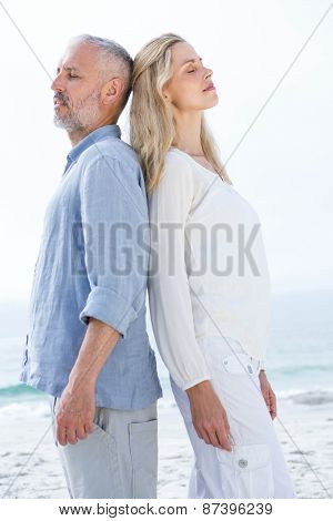 Happy couple standing back to back at the beach