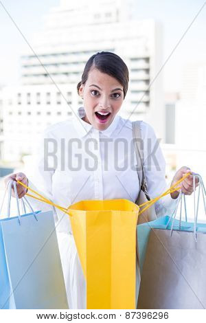 Surprised woman looking in shopping bag outside