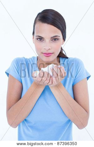 Pretty woman suffering from cold holding tissue on white background