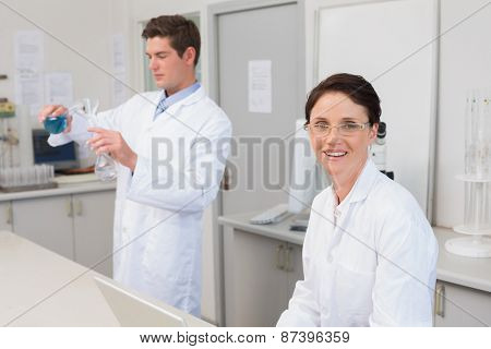 Scientist working attentively with laptop and another with beaker in laboratory