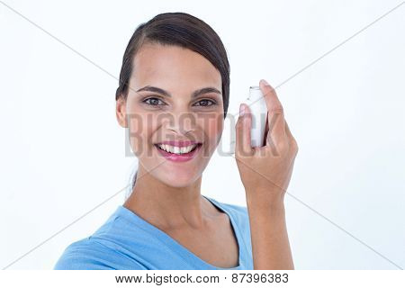 Smiling woman using her inhaler on white background