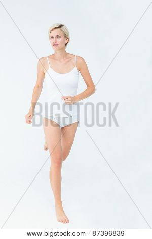 Smiling blonde woman running on white background