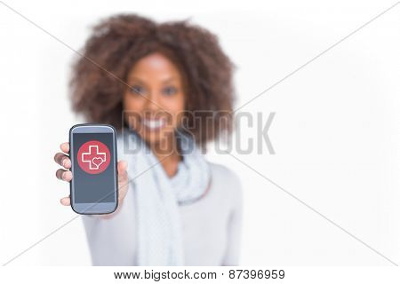 Woman with afro showing her smartphone against heart and cross