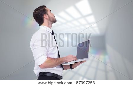 Sophisticated businessman standing using a laptop against room with windows at ceiling