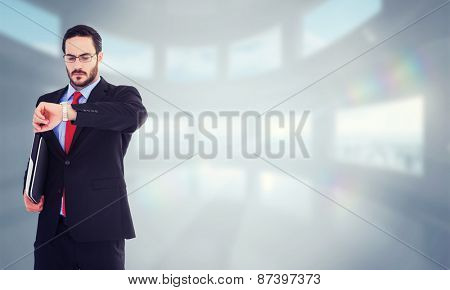 Frowning young businessman checking time against bright white room with windows