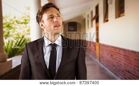 Young businessman thinking and looking up against hallway
