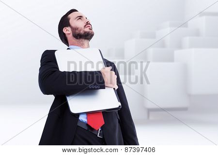 Concentrating businessman in suit holding laptop against abstract white design