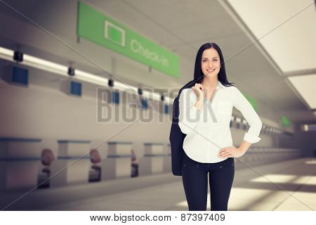 Pretty businesswoman smiling at camera against airport