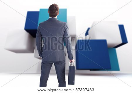 Businessman standing with his briefcase against abstract background