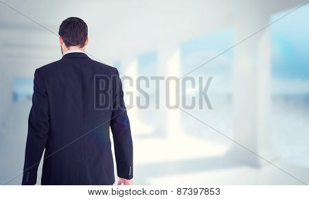 Rear view of businessman holding a briefcase against bright white room with columns