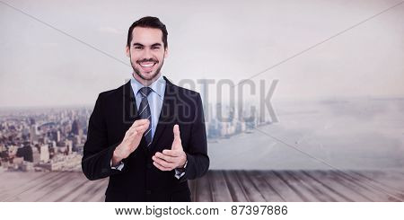 Happy businessman standing and applauding against city scene in a room