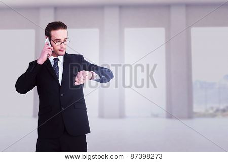 Serious businessman phoning while checking time against room overlooking ocean