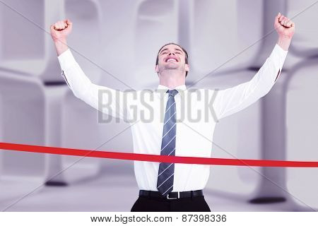 Happy businessman crossing the finish line against white abstract room