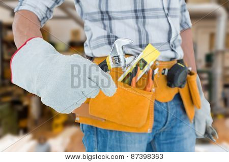 Technician using adjustable wrench against white background against workshop